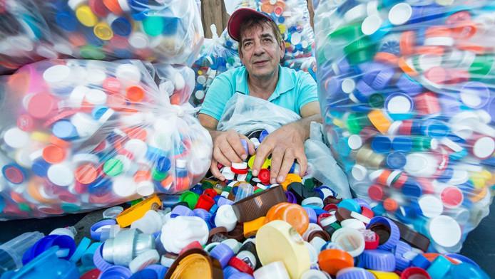 """Arend Heilbron tussen de tienduizenden plastic doppen die hij heeft ingezameld. ,,De loods betaal ik zelf."""""""