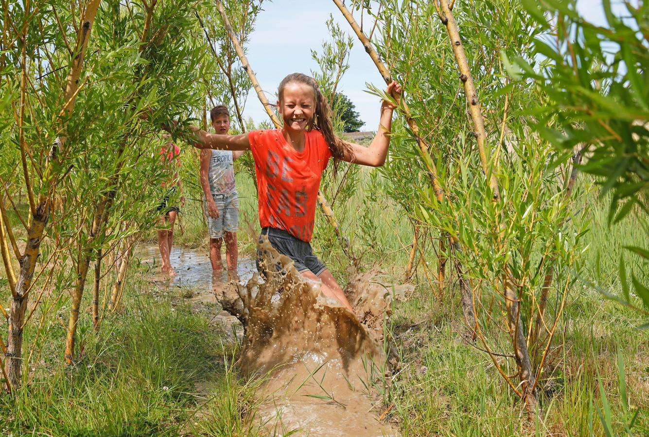 Dide Klok (11) leeft zich uit in de modder op het blotevoetenpad.