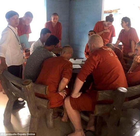 De mannelijke toeristen die in Cambodja vastzitten voor 'dirty dancing' zijn kaalgeschoren en dragen oranje gevangenispakken.