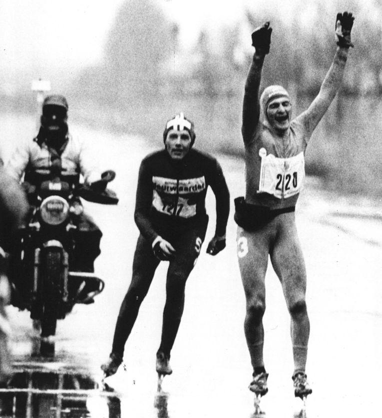 Evert van Benthem gaat met opgeheven armen over de streep tijdens de Elfstedentocht van 1986. Beeld Anp
