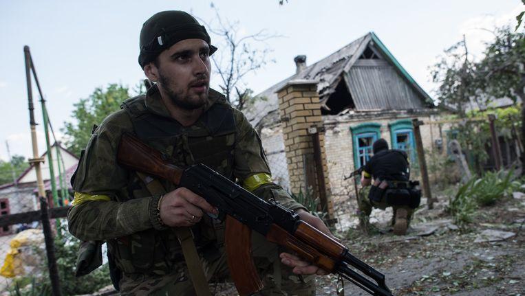 Een Oekraïense soldaat op patrouille, vandaag in Marinka in Oost-Oekraïne. Rebellen voerden gisteren een grootschalige aanval uit op het plaatsje vlakbij Donetsk, maar wisten het niet in handen te krijgen. Beeld ap