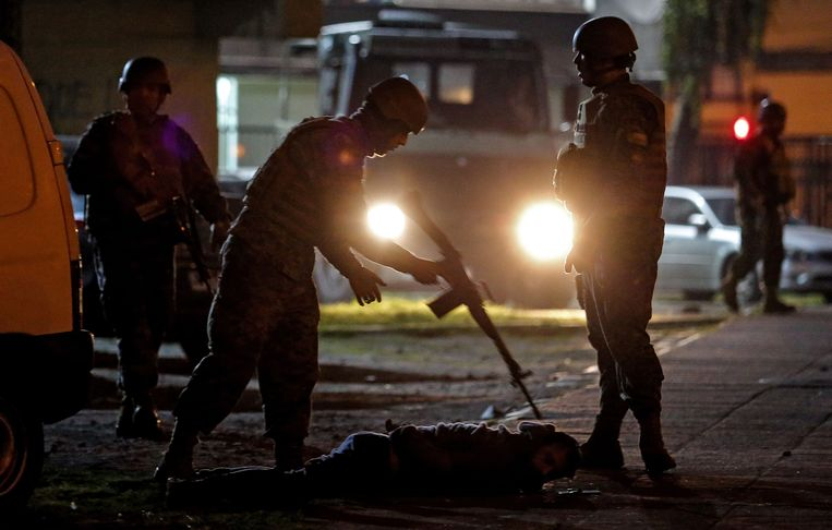 Soldaten arresteren een demonstrant in de stad Concepcion. Beeld null