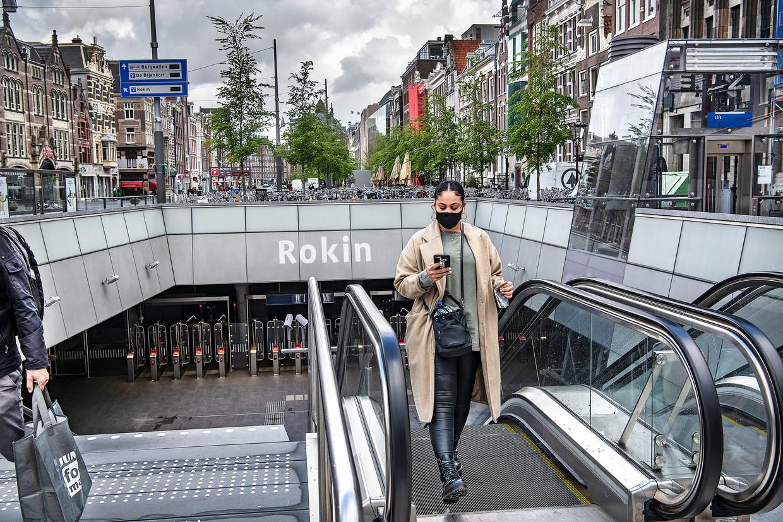 Een vrouw met een zwart mondkapje arriveert op een vrijwel verlaten Rokin in Amsterdam. Straks is iedereen verplicht een mondkapje te dragen in het ov. Beeld