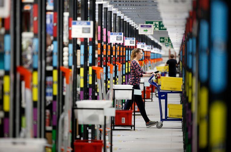 Een 'orderpicker' verzamelt producten uit de schappen van een vestiging van Amazon ten noorden van Londen. Beeld AFP