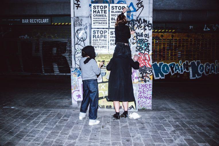 Drie jonge vrouwen trekken anoniem de straat op om affiches op te hangen. Beeld Francis Vanhee