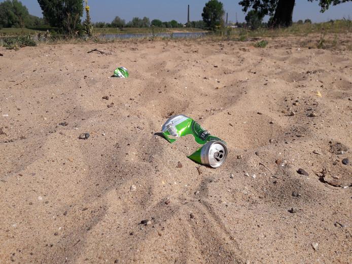 Lege blikjes in het zand.