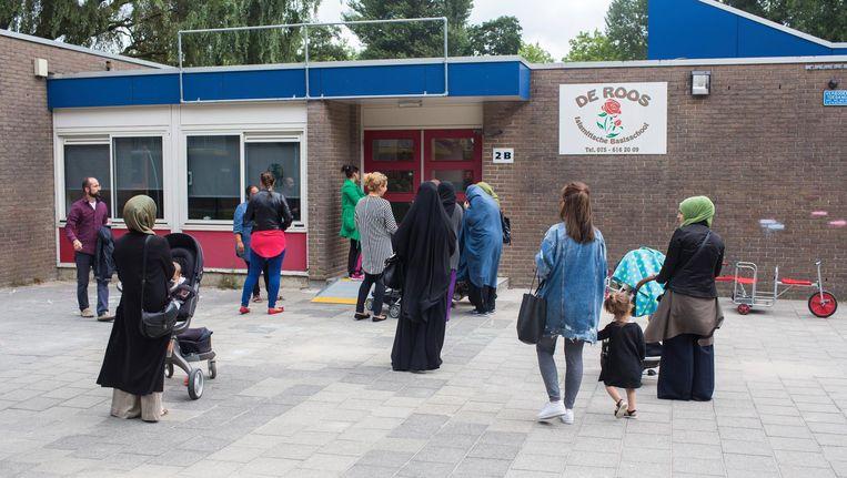 Ouders en kinderen op het schoolplein van basisschool De Roos. De Zaanse school zou gelieerd zijn aan Gülen. Beeld Ton Koene