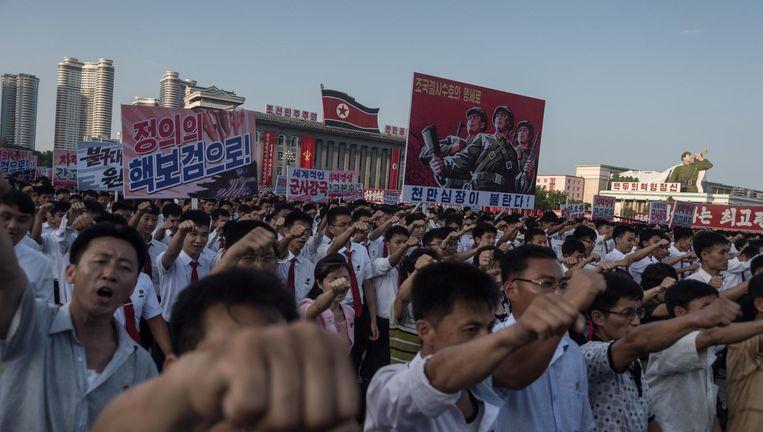 Mensen met spandoeken tijdens een mars tegen de VS in Pyongyang, Noord Korea. Beeld afp