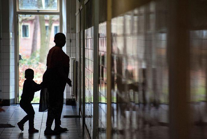 Een bewoonster van het asielzoekerscentrum loopt met haar zoontje door de gang van een van de gebouwen in Gilze.