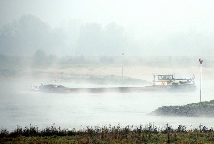 Een vrachtschip baant zich tussen Ooij en Gendt door de mist een weg richting Duitsland. Archieffoto.