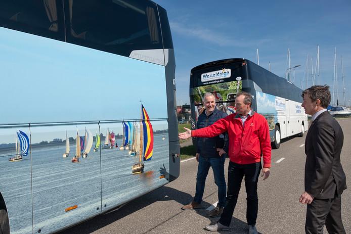 Paul de Baar, Marco van Dijke en burgemeester Huub Hieltjes van Kapelle kijken naar één van de bussen met Wemeldingepromotie.