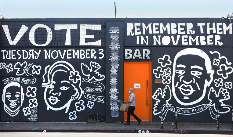 Graffiti op een muur in Los Angeles met een portret van George Floyd, Breonna Taylor en Ahmaud Arbery - drie zwarte slachtoffer van politiegeweld - en de oproep om op 3 november te gaan stemmen.  Beeld AFP