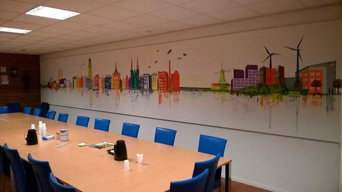 """Skyline Deventer ,,Deze """"wandschildering"""" heb ik mogen maken in opdracht voor PHB bouwbedrijf Deventer. Het hangt in hun kantine en meet 9,30 m x1,50m. Het is een min of meer abstracte skyline van Deventer met helemaal rechts hun eigen kantoorgebouw'', vertelt Marian Blanke van Bordenzo"""