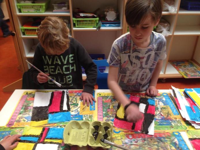 Groep drie leerlingen werken aan schilderijen die naar Italië worden opgestuurd.