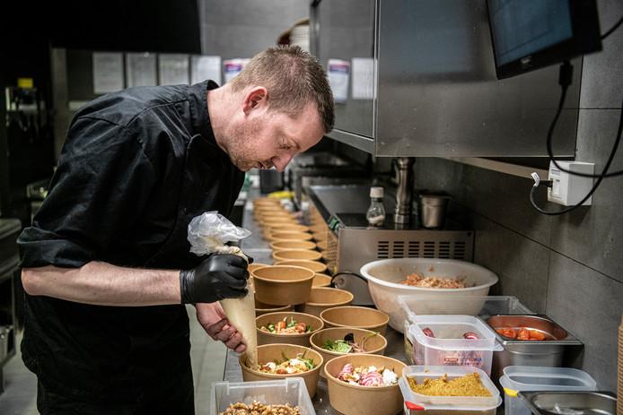 Een kok van restaurant Zaal 4 in Wijchen legt de laatste hand aan gerechten die bezorgd moeten worden.