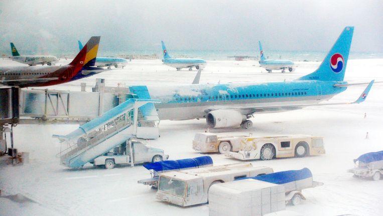 Vliegtuigen en landingsbaan bedekt met sneeuw op het vliegveld van Jeju-eiland. Beeld reuters