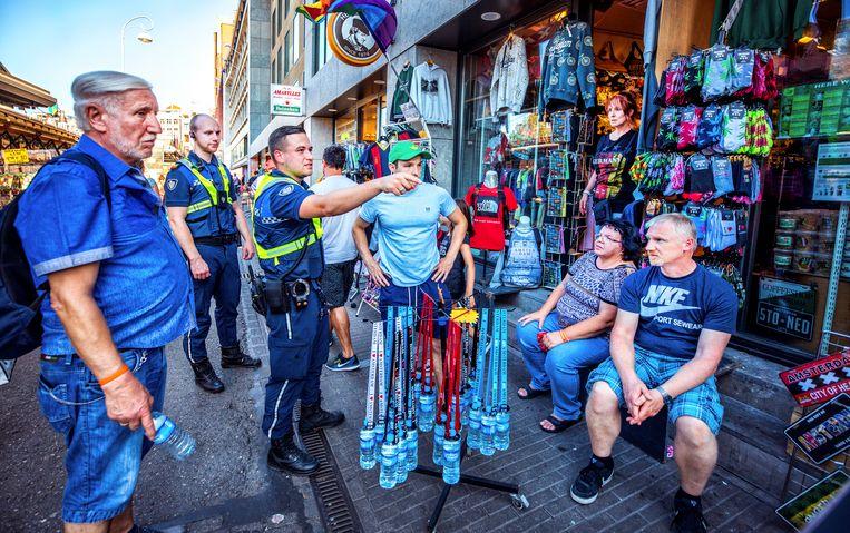Handhavers Job (links) en Vadym tijdens hun ronde op de Bloemenmarkt in Amsterdam.  Beeld raymond rutting / de volkskrant