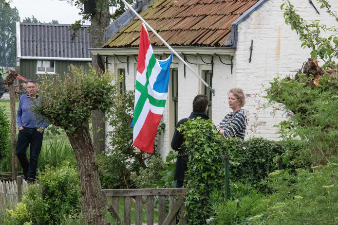 De Groningse vlag hangt halfstok in Westerwijtwerd. Buurtbewoners praten buiten na.