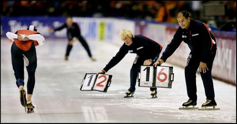 De schaatscoaches Ab Krook (rechts) en Wopke de Vegt tijdens een wereldbekerwedstrijd in Heerenveen in 2005. Op de baan passeert Carl Verheijen. Beeld Jiri Büller