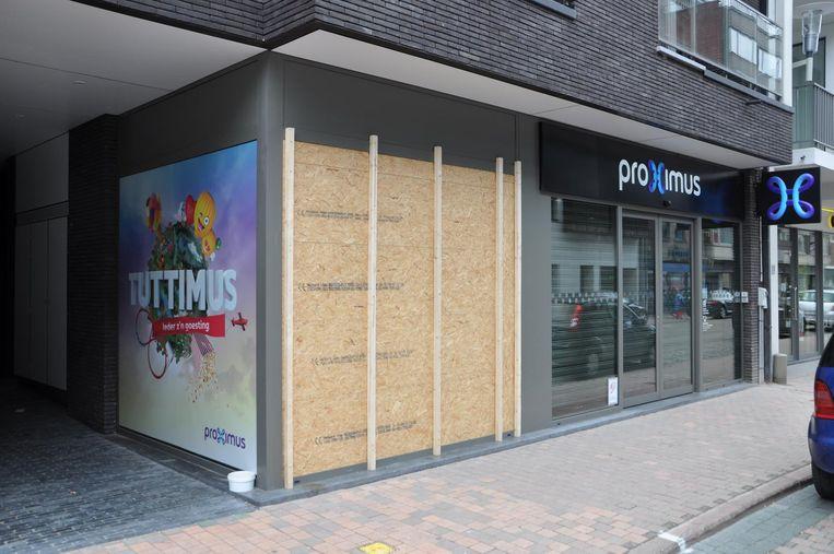 De stukgeslagen vitrine van de Proximuswinkel in Deinze is dichtgemaakt met houten panelen.