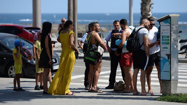 Een agent spreekt met toeristen in Barcelona. Beeld afp