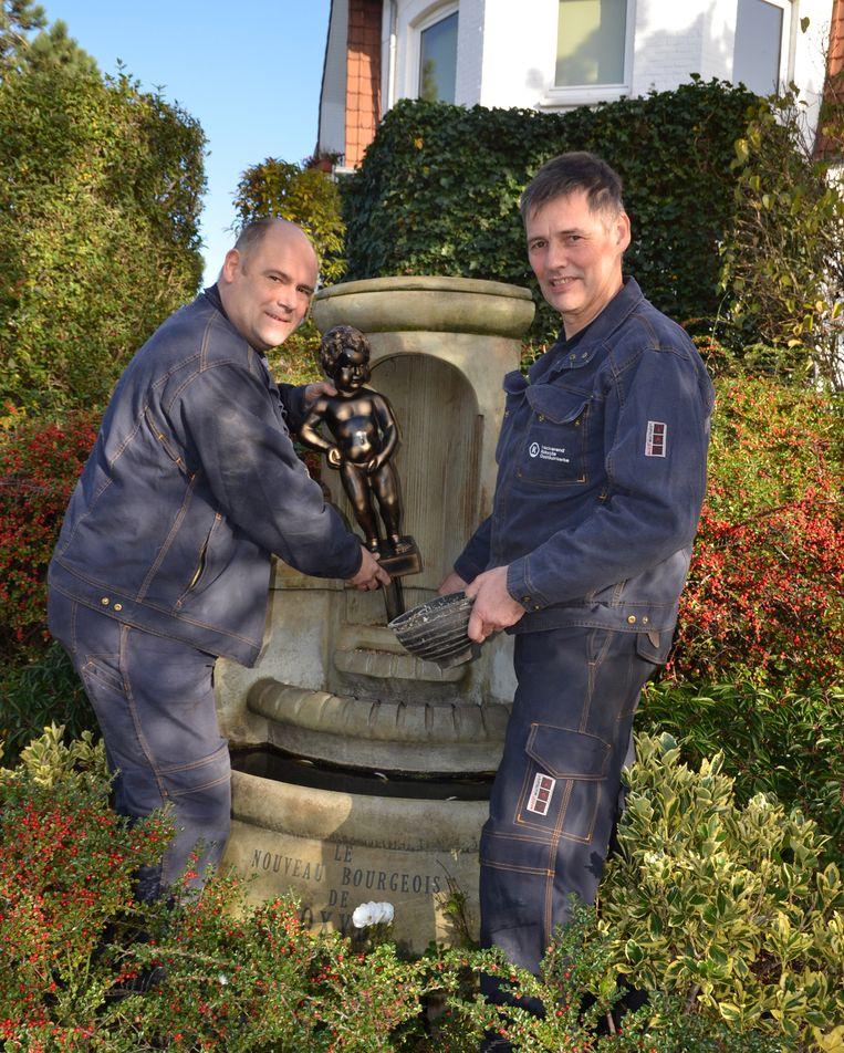 Peter Dalle en Marc Debergh plaatsen het beeld van Manneke Pis terug.