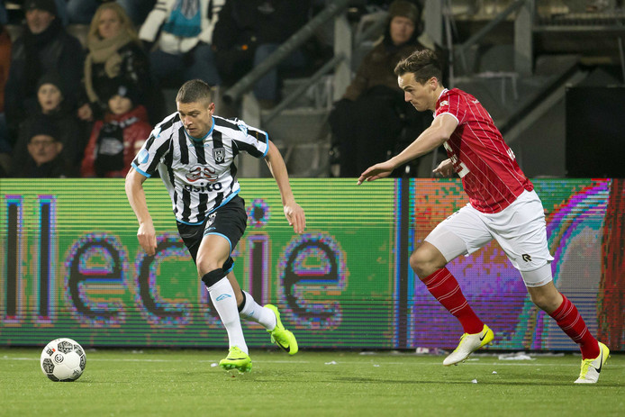 Heracles-speler Kristoffer Peterson (links) in duel met Willem II'er Freek Heerkens.