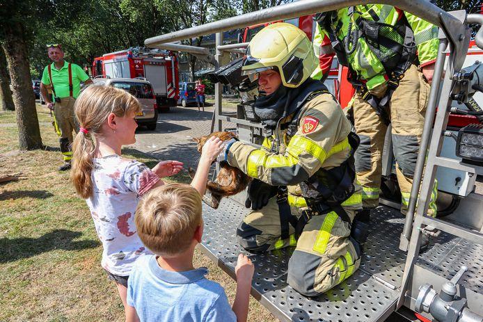 Brandweerman Bartjan van de Belt overhandigt de verhitte kat Saartje aan het jonge baasje.