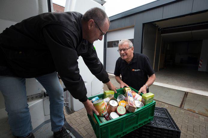 Peter Bob Peerenboom (rechts) en chauffeur Robert Lucassen laden een voedselpakket in de bus bij de Voedselbank Doetinchem.