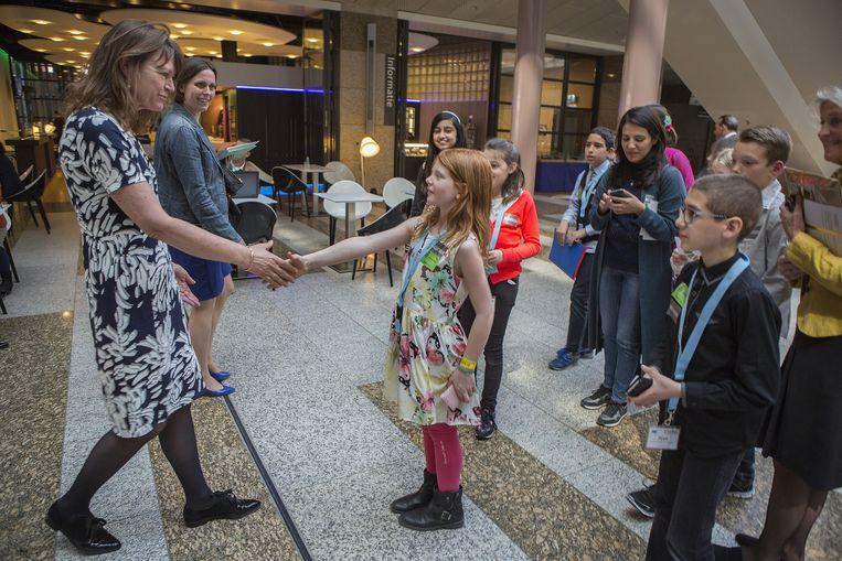 Margrite Kalverboer wordt na haar beëdiging op 20 april als Kinderombudsman in de Tweede Kamer opgevangen door jonge ambassadeurs van de Kinderrechten. Beeld null