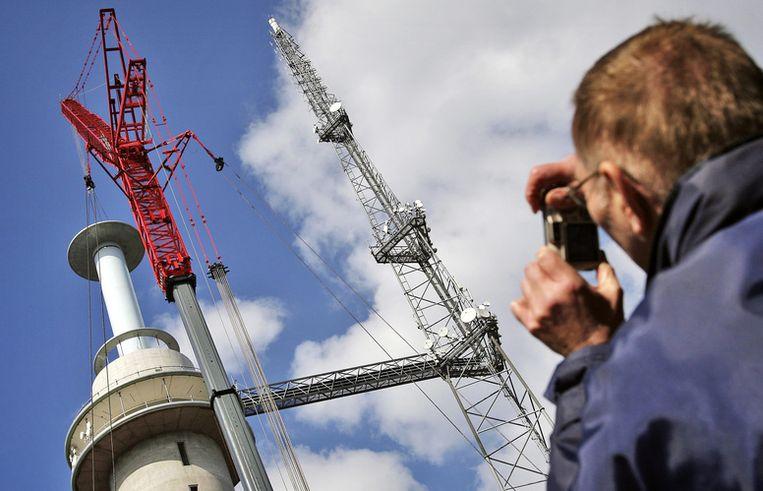 Met een van de grootste bouwkranen ter wereld worden maandag mastdelen op de zogenaamde KPN toren in Amsterdam gehesen. Foto ANP/Koen van Weel Beeld