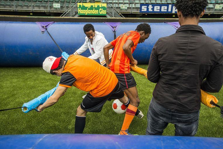 Negentig alleenstaande minderjarige vreemdelingen (amvérs) waren woensdag op bezoek in het stadion vanADODen Haag. Ze konden zich vermaken met een potje 'tafelvoetbal' of het nemen van strafschoppen onder leiding van ADO-spelers. Beeld Jiri Büller