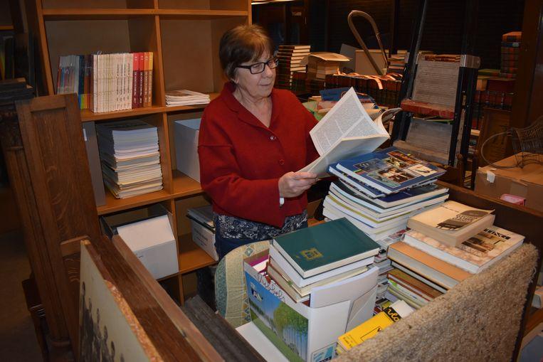 Marie-Jeanne snuistert in één van de boeken.
