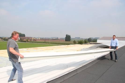 Zaakvoerder Dominiek Vandenberghe en hulp in nood Bart Wackenier tillen een plaat op het dak op.