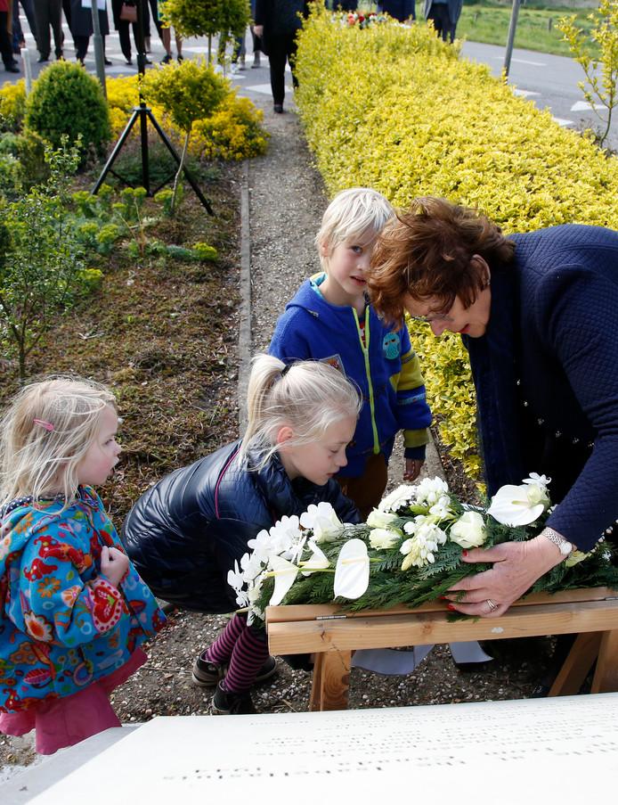 Rian de Feijter (rechts) legt in 2017 met kinderen uit Philippine bloemen bij het oorlogsmonument aan de Isabellaweg.