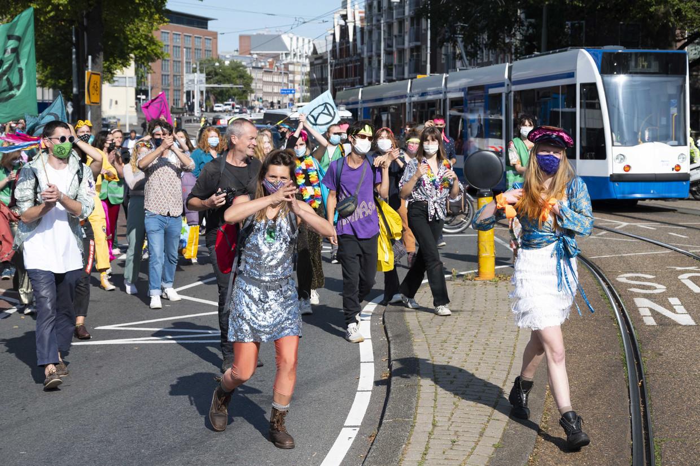 Demonstranten tijdens een actie van Extinction Rebellion gaan dansend door het centrum van Amsterdam. Beeld ANP