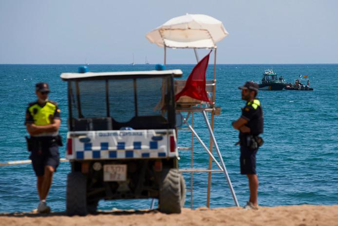 De politie ontruimt het strand.