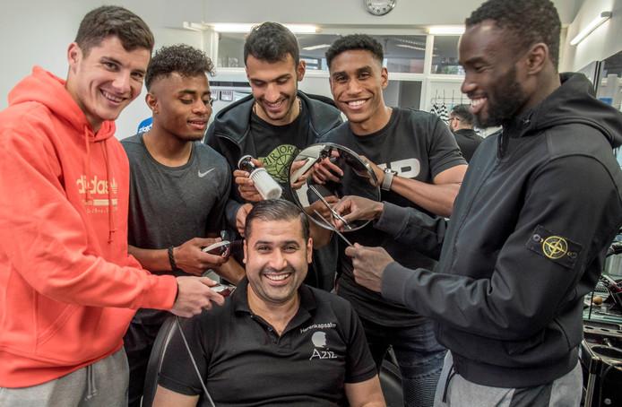 """Even de rollen omgedraaid: Aziz Elmahi in de kappersstoel. Vrijdagmiddag - daags voor de bekerfinale - kwamen Vrousai, Palacios, Pavlidis, Saddiki en Lewis langs voor een knipbeurt. ,,Hij is gewoon de beste kapper."""""""