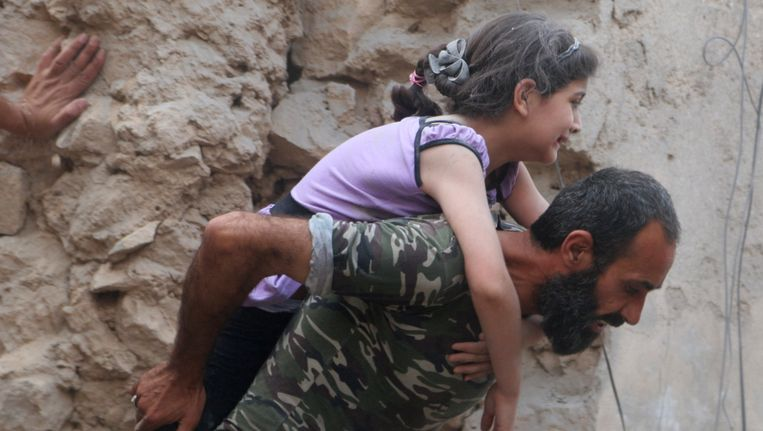 Een Syrische man draagt een gewond meisje in Aleppo. Luchtaanvallen in het noordwesten van Syrië hebben vrijdag aan zeker 23 mensen het leven gekost. Beeld reuters