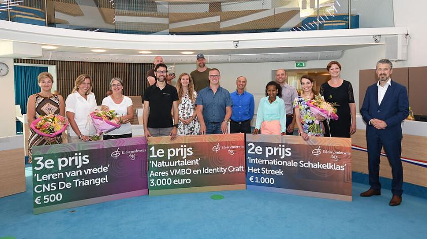Wethouder Meijer (rechts) poseert met de winnaars van de Edese Onderwijsprijs.