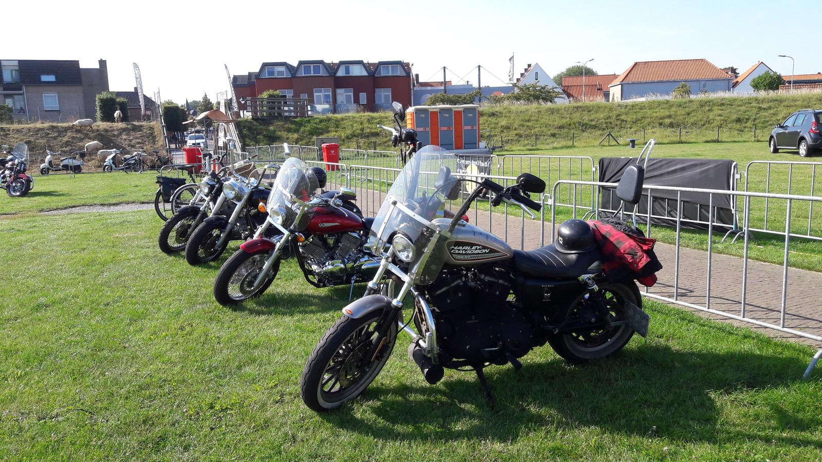 Motorrijders parkeren hun voertuig keurig op een strook buiten het festivalterrein op de Karolingenburcht in Oost-Souburg.