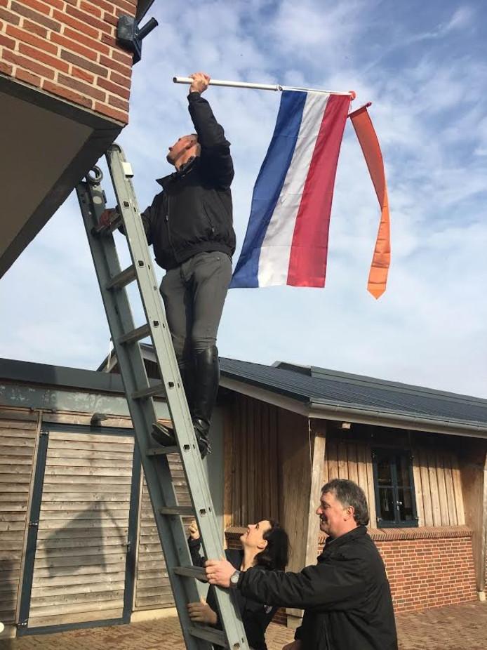 Gert-Jan Bruggink hangt de vlag in top, zijn vriendin Pia-Luise Aufrecht en stalmanager Martin Engbers houden de ladder vast.