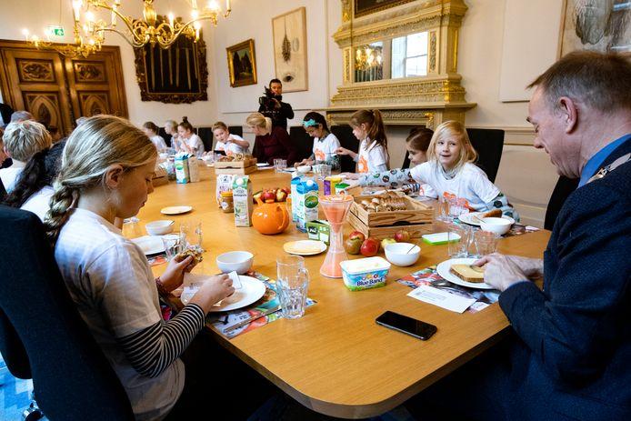 De kinderen van de Oudaen schuiven bij burgemeester König aan voor een gezond ontbijtje.