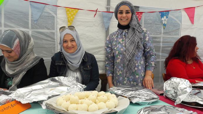 De Syrische Baraah Alkhaled (staand)n met haar kokos-amandelballen.