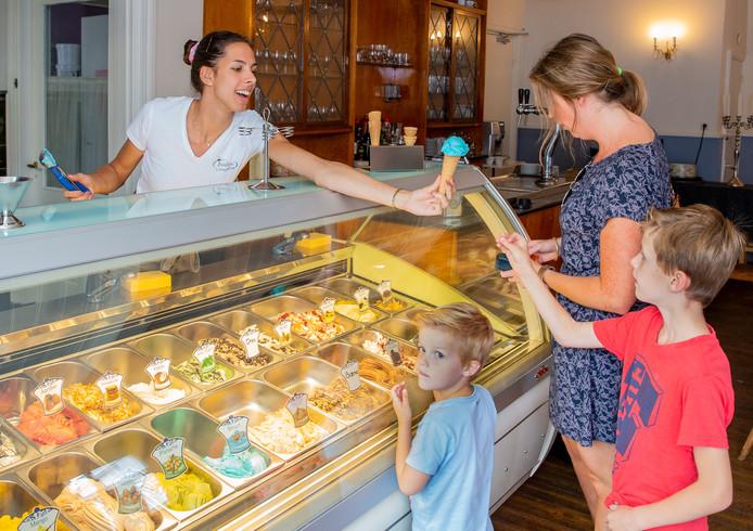 Een medewerker van IJssalon Juultje in Druten voorziet kinderen van een smurfenijsje.