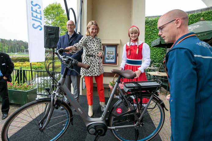 Staatssecretaris Van Veldhoven en Roodkapje komen aanfietsen op de Sjees Fiets waarvan het eerste exemplaar aan een medewerker van de Efteling geschonken word.