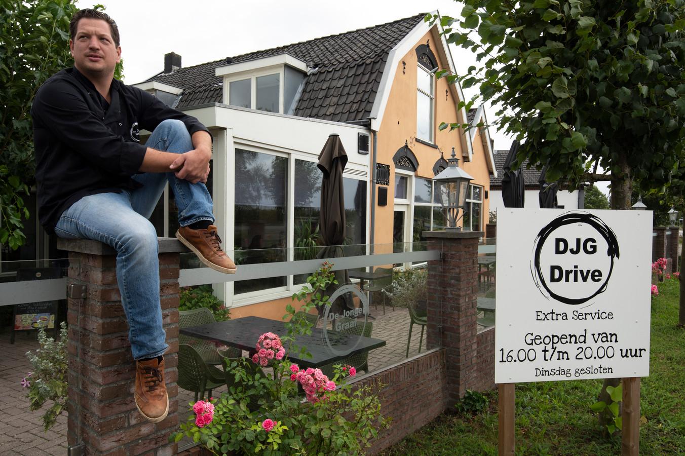 Patrick Terschegget bij een van de gewraakte borden die voorbijgangers attenderen op zijn afhaal- en bezorgservice.