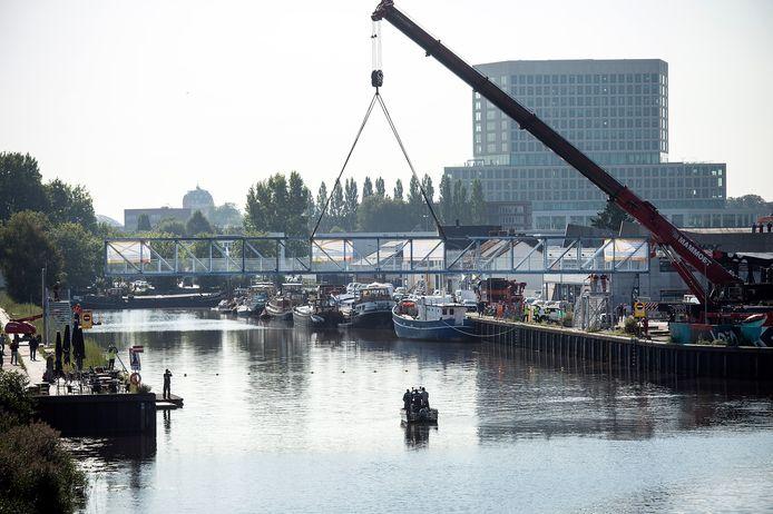 Met een enorme kraan wordt de loopbrug over de Belcrumhaven in Breda erin gehangen. De Veilingkade en het Havenkwartier zijn nu verbonden.
