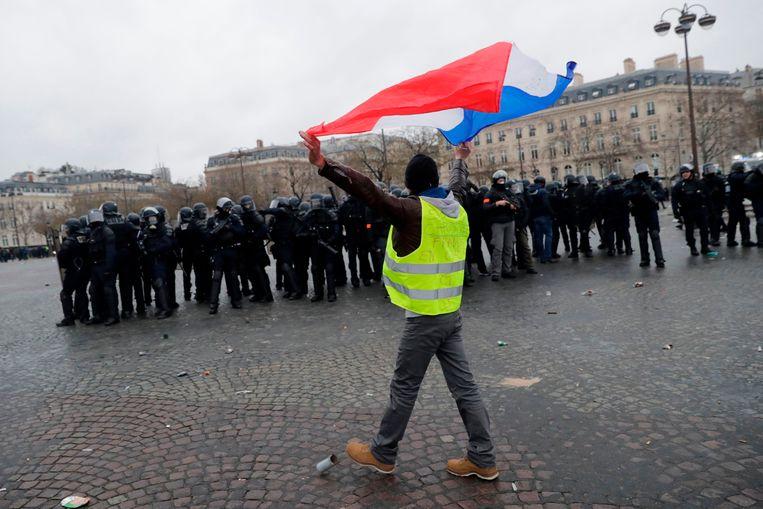 Een demonstrant zwaait met de Franse vlag.