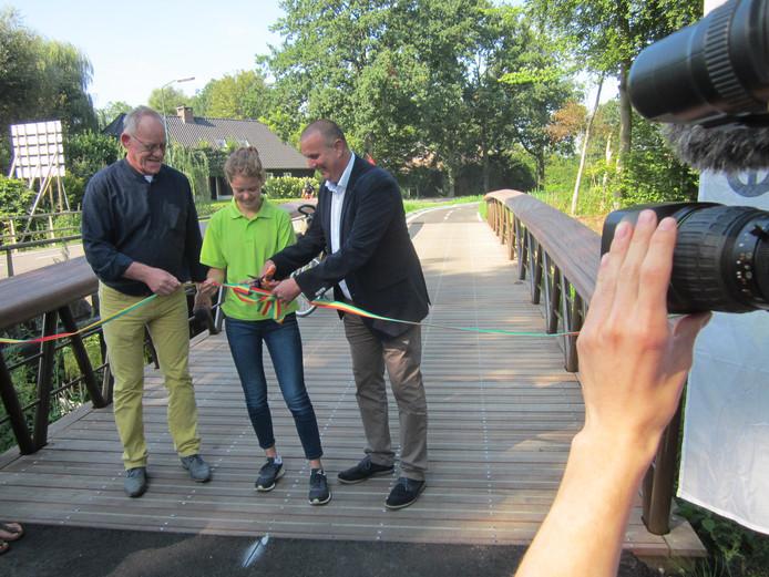 Peter van de Wouw (Moergestel Fiets- en Wandeldorp), Inge van den Boer en wethouder Dion Dankers openen op de nieuwe brug over de Reusel het opgeleverde fietspad van Moergestel naar Haghorst.